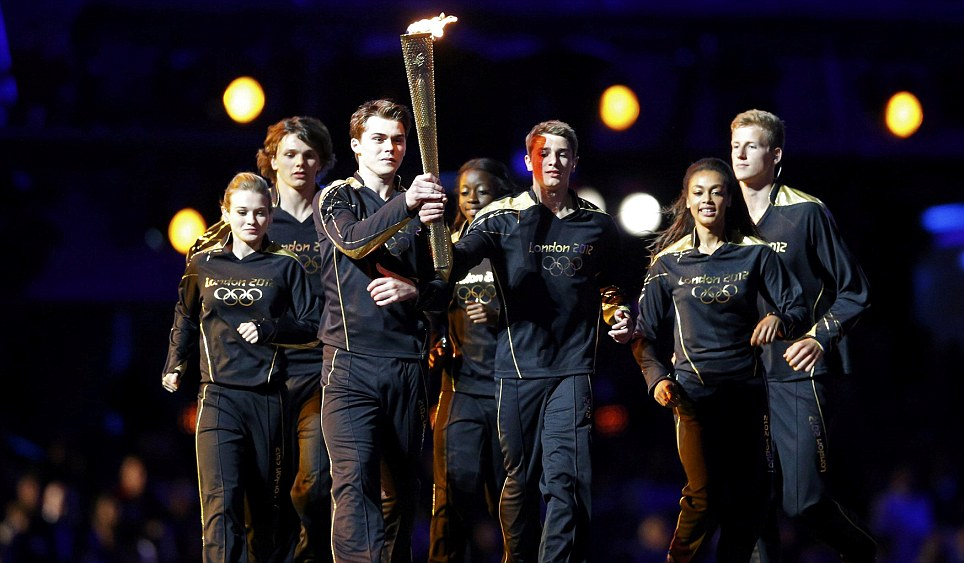 Seven young athletes carry the Olympic torch into the opening ceremony of the London 2012 Olympic Games