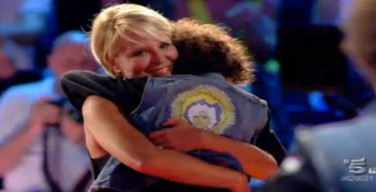 Un bambino concorrente abbraccia Maria De Filippi