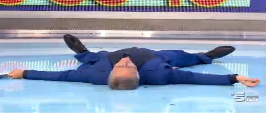 Paolo Bonolis a terra, sfinito dai concorrenti