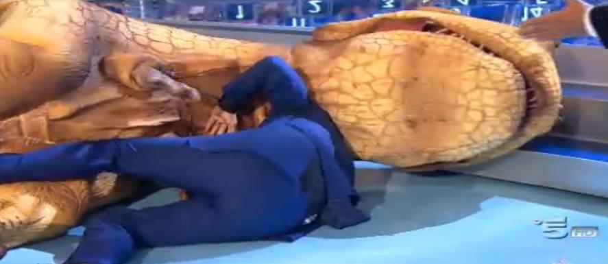 Paolo Bonolis trascinato a terra dal dinosauro